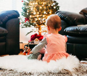 toddler sitting in front of Christmas tree brooklyn family photographer